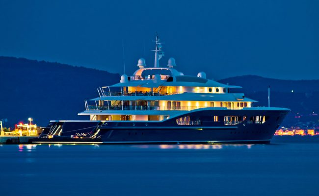 Blue mega yacht at night shutterstock_204217804